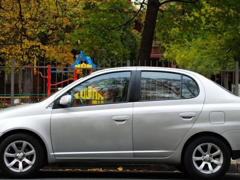 Серебристый седан Toyota Echo, вид сбоку