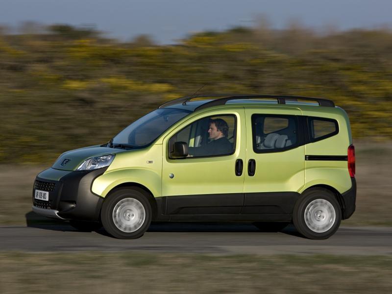 Зеленый минивэн Peugeot Bipper на трассе