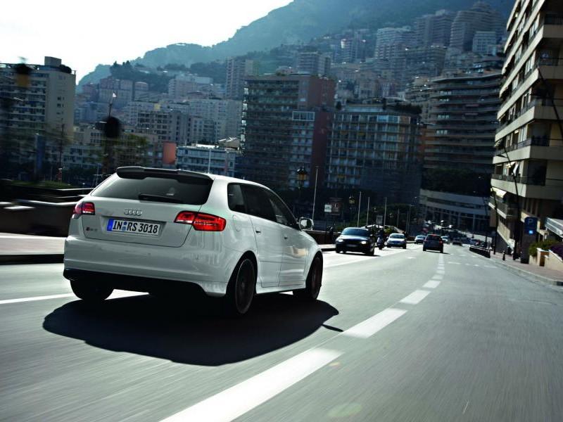Белый хэтчбек Audi RS3 Sportback, вид сзади, на трассе