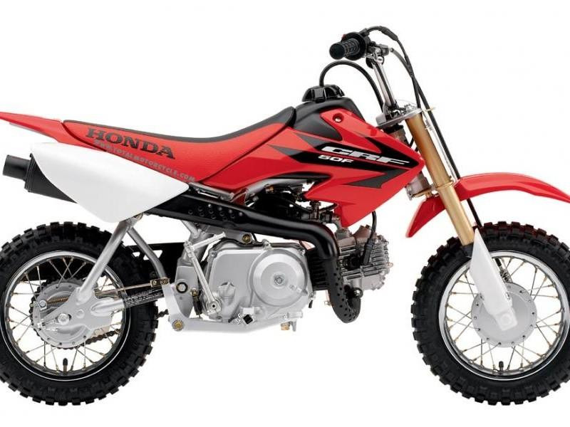 Красный мотоцикл Honda CRF50F вид сбоку