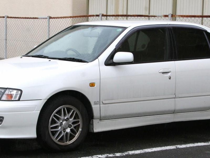 Белый седан Nissan Primera Camino вид сбоку