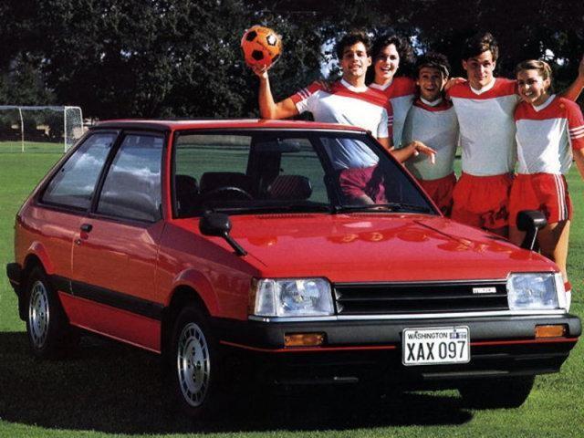 Малиновая Mazda Familia: вид спереди справа