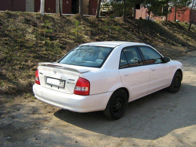 Белый Mazda Familia вид сзади