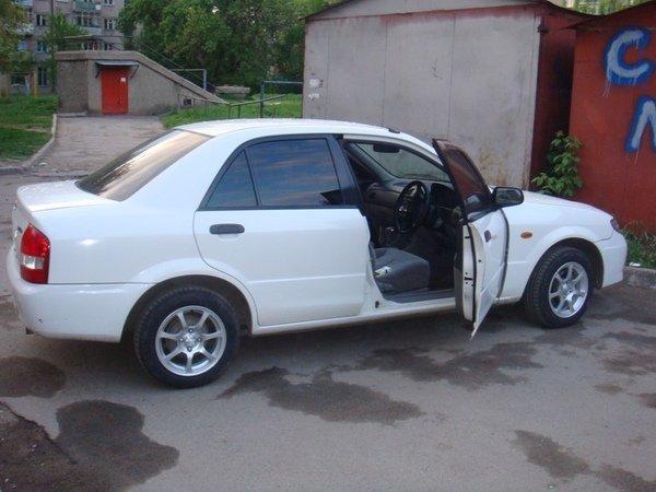 Белый седан Mazda Familia вид сбоку