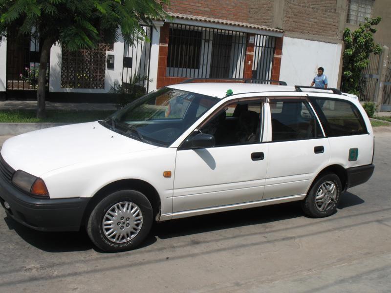 Белый универсал Nissan Avenir, вид сбоку