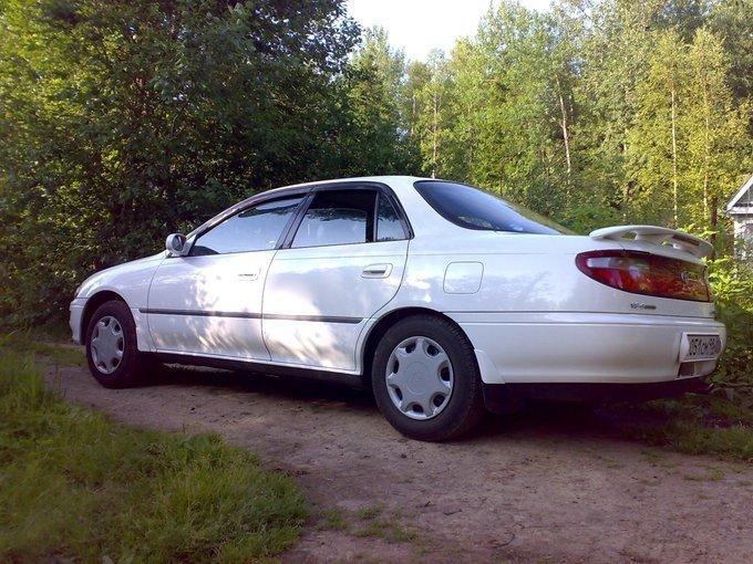 Белый Toyota Carina вид сбоку