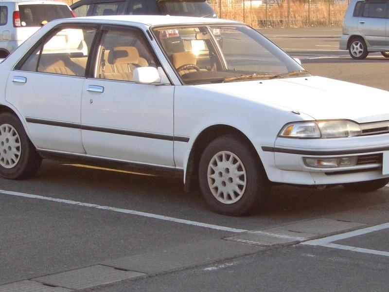 Белый седан Toyota Carina, вид сбоку