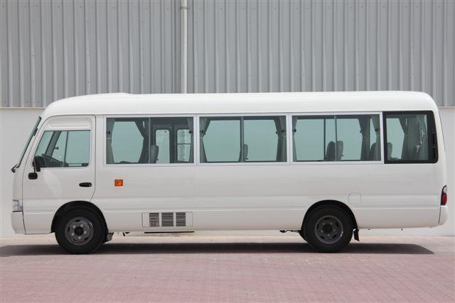 Белый автобус Toyota Coaster, вид сбоку