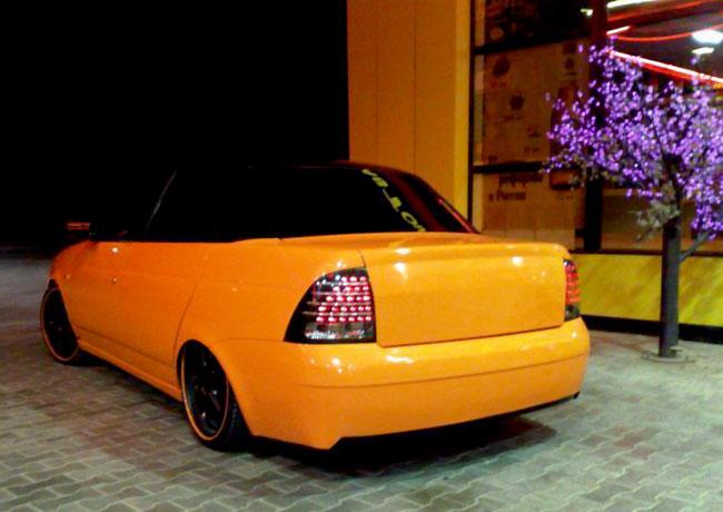 Оранжевая Лада Приора с тюнингованными фарами: вид сзади слева